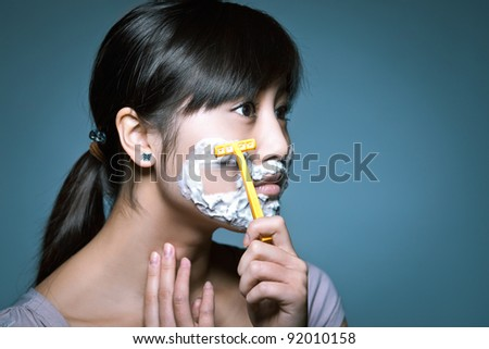 A young Asian girl shaving in a funny role reversal. - stock photo
