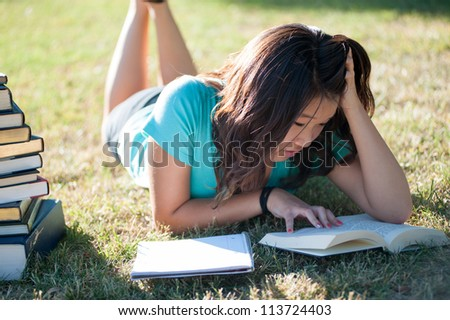 A young Asian girl studying outside in the grass - stock photo