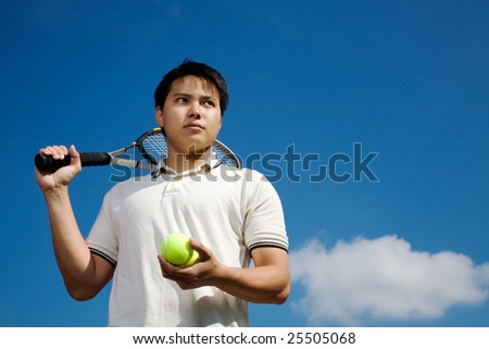 A young asian male tennis player outdoor - stock photo
