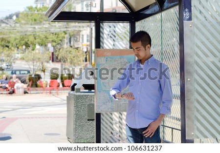 A young Asian man at a bus stop checking his watch as he waits - stock photo