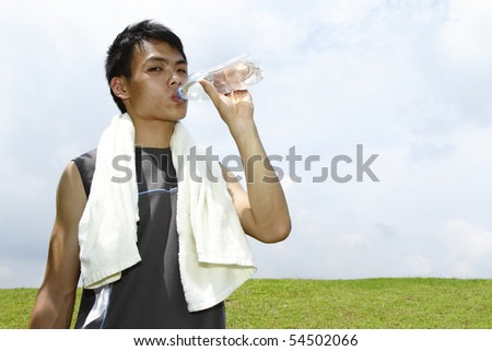A young Asian man drinking after a work-out - stock photo