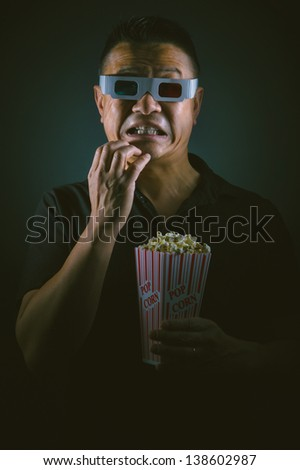 A young Asian man  in an entertainment setting appearing shocked. - stock photo