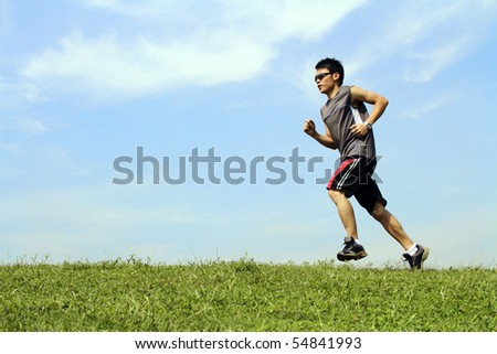 A young Asian man running on grass - stock photo