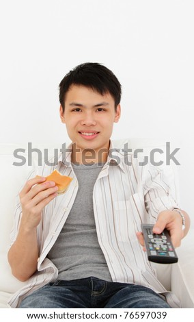 A young Asian man with a TV remote and burger - stock photo