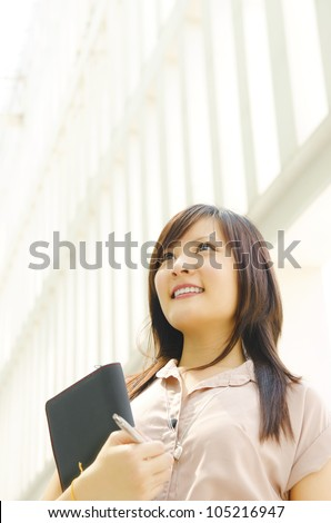 A young Asian woman looking far away to bright light in front of a modern office building, with diary on hand. - stock photo