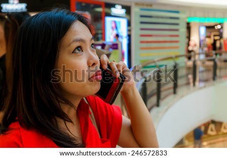 A young asian woman showing her sad face while talking on the phone. Shallow dof, selective focus on the woman's face - stock photo