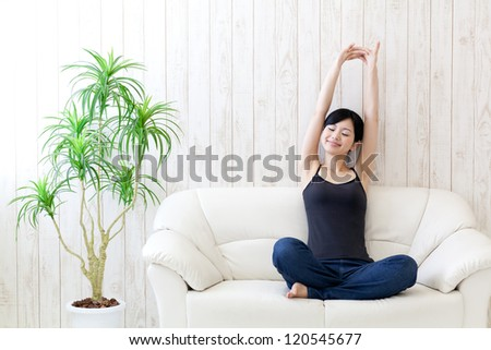 a young asian woman stretching in the room - stock photo