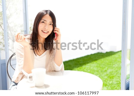 a young asian woman using smart phone in cafe - stock photo