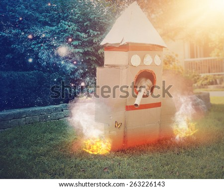 A young astronaut child is sitting in a cardboard space rocket ship pretending to explore. She is in the front yard imagining she is in space with stars - stock photo