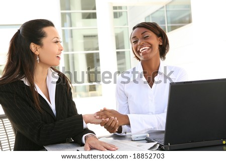 A young attractive and diverse women business team with computer - stock photo