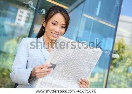 A young attractive asian business woman reading  newspaper - stock photo