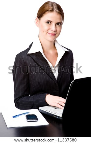 A young attractive businesswoman with laptop at a desk - stock photo