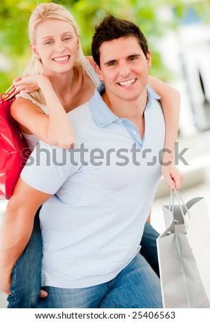 A young attractive couple together outside with shopping bags - stock photo