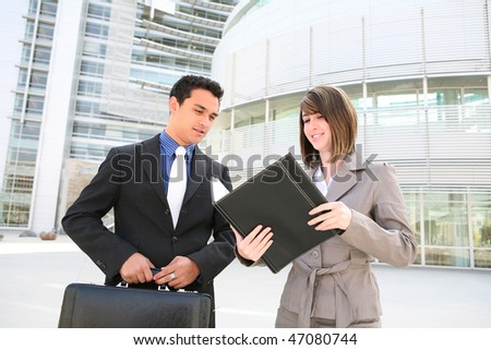 A young, attractive man and woman business team at their office building - stock photo