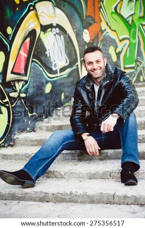 A young attractive man sitting down outside, wearing a black jacket and blue jeans - stock photo