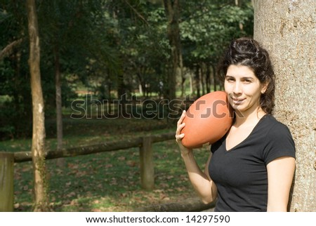 A young, attractive woman is standing next to a tree at the park.  She is smiling and holding a football on her shoulder.Horizontally framed photo. - stock photo