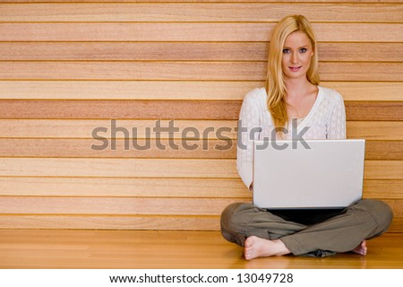 A young attractive woman using laptop and phone at home on wooden floor - stock photo