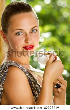 A young attractive woman with a cup of coffe  near the window - stock photo