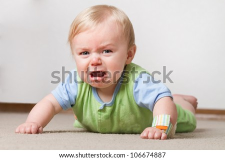 A young baby having a fit on the ground crying and making a pout face - stock photo