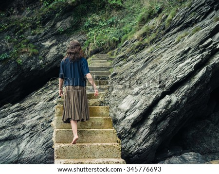 A young barefoot woman is walking on some stairs leading up a cliff - stock photo