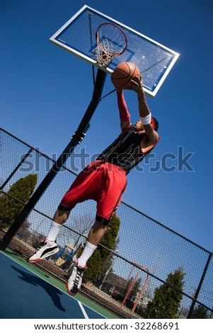 A young basketball player driving to the hoop with some fancy moves. - stock photo