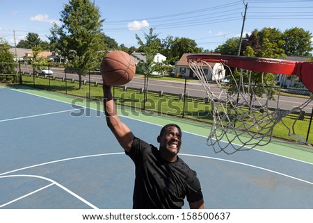 A young basketball player dunking a basketball as seen from rim level. - stock photo