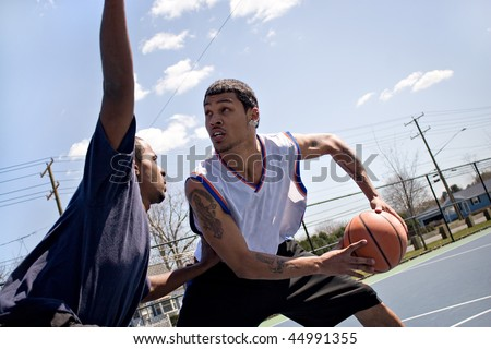 A young basketball player guarding his fierce opponent. - stock photo