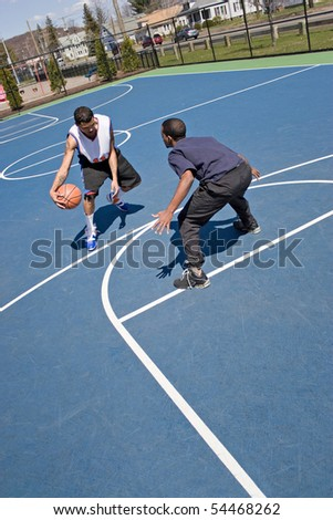 A young basketball player guards his opponent during a one on one basketball game at the park. - stock photo