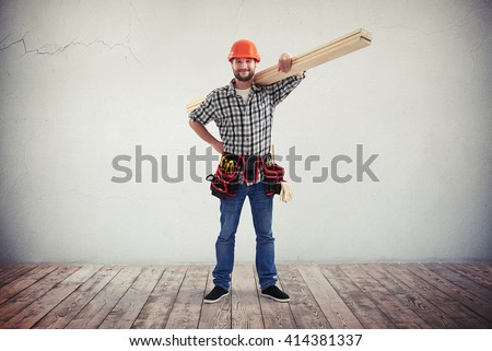 A young bearded workman in casual clothes, hard hat and utility belt is holding some wooden boards on his shoulder - stock photo