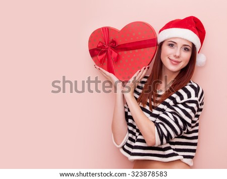A young beautiful caucasian girl in Santa Claus hat with gift box on pink background - stock photo