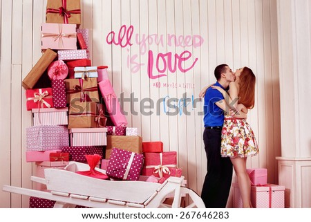 A young beautiful couple is kissing near a wall with gift boxes and caption love. - stock photo