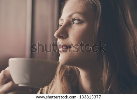 A young beautiful girl with a cup of tea, cappuccino toning - stock photo