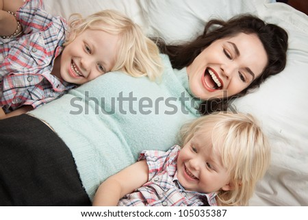 A young beautiful happy mother having fun with her two cute children - stock photo