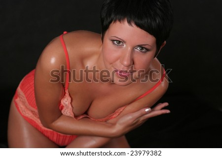 A young beautiful smiling woman wearing underwear standing over black background - stock photo