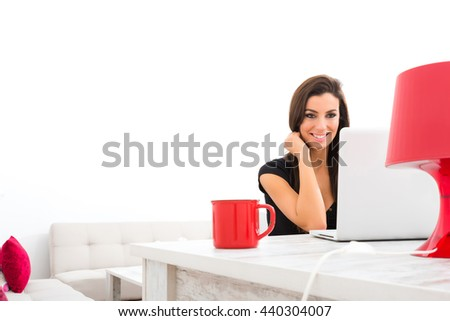 A young beautiful woman being cheerful while using a Laptop computer at home.