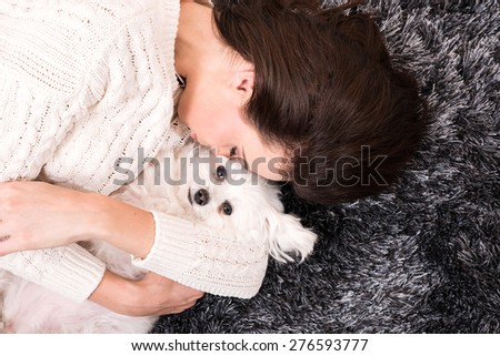 A young beautiful woman cuddling her Dog on the carpet in the living room.  - stock photo