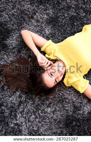 A young, beautiful woman in underwear lying at home on the carpet listening to music with earphones.  - stock photo