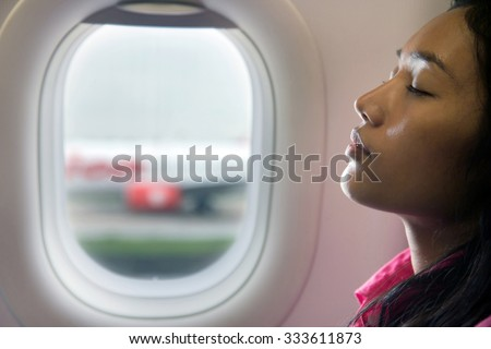 A young beautiful woman resting on airplane beside window. Portrait of a woman sitting on a plane next to a window. Passenger relaxes on takeoff. The traveler sleeps in the plane after landing. - stock photo