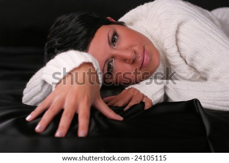 A young beautiful woman with a light smile  wearing white sweater lying on the bed covered with black cloth - stock photo