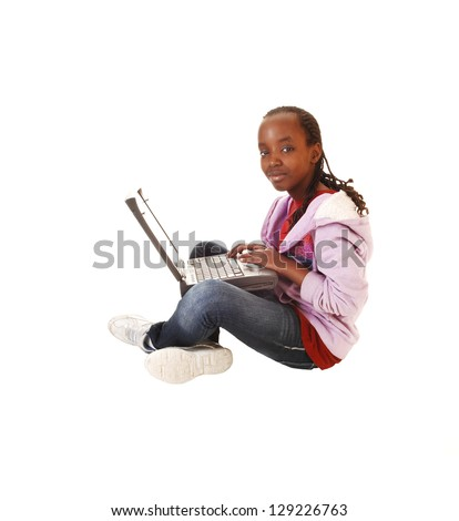 A young black teen girl sitting on the floor with her laptop on her lap, in jeans and snickers, for white background, doing homework on the computer. - stock photo