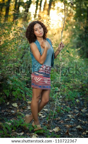 A young black woman gazes into the distance in a forest. - stock photo