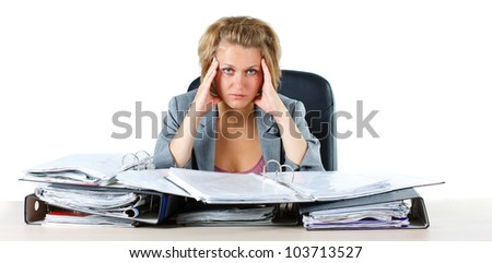 A young blond businesswoman sitting behind her desk with folders, looking overworked, stressed, tired, looking into camera - isolated on white - stock photo