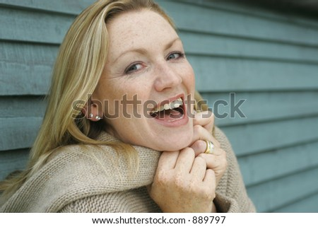 A young blond woman laughing outside - stock photo
