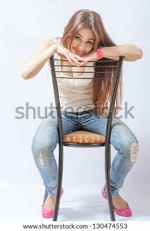 A young blond woman resting on a chair in a white blouse and blue jeans for white background in the studio. - stock photo