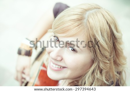 A young blonde woman playing the guitar happy. - stock photo