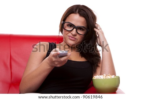 A young bored woman is sitting on a sofa flicking trough TV channels and eating popcorn. Bored woman watching TV. - stock photo