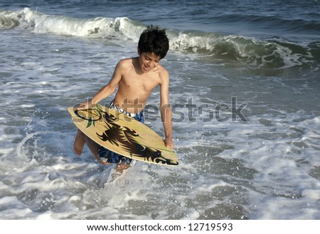 A young boy about to jump on a skim board. - stock photo