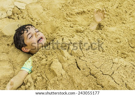 A young boy buried in the sand at the beach - stock photo