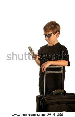 a young boy checks his cell phone as he is traveling with his suit case isolated on white with room for text - stock photo