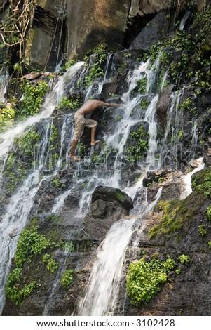 A young boy climbing up a jungle waterfall - stock photo